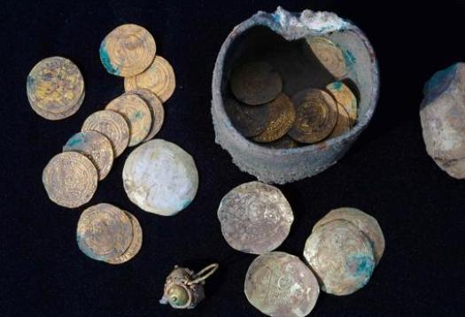 El pendiente y las monedas halladas en el cofre