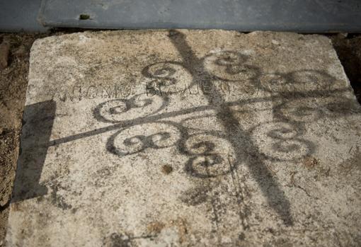 Restos de la lápida partida, a un lado de la tumba