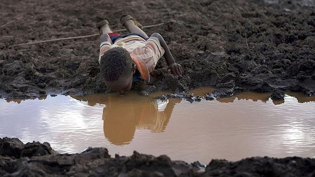 Un niño bebe agua en un charco de la aldea etíope de Bule Duba