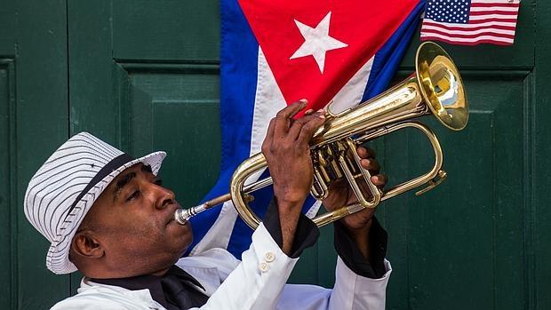 Un cubano toca la trompeta junto a una bandera de su país y otra de EE.UU., en La Habana