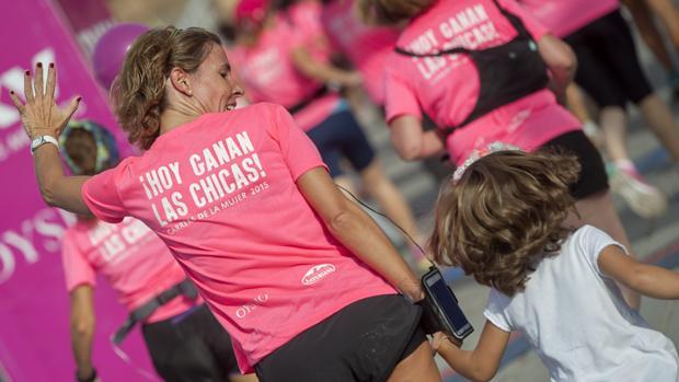 Una madre corre con su hija en la carrera de la mujer en Sevilla