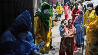 Women in India line up to be tested for coronavirus.