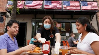 Two Americans are eating in a restaurant while their waiter is wearing a mask.