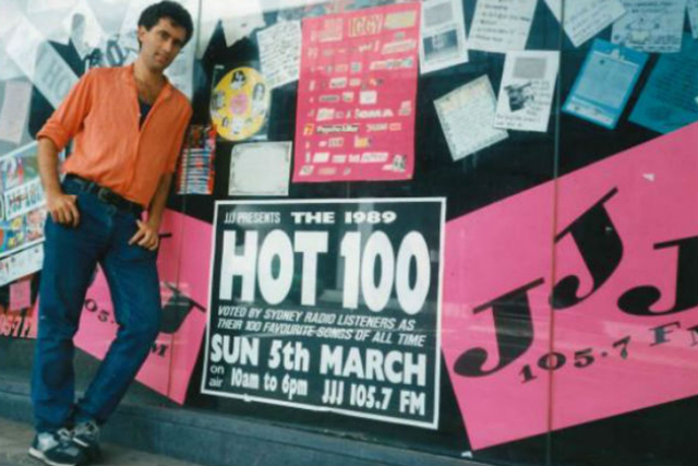 triple j intern Lawrie Zion, who came up with the idea for the countdown, posing by promotional artwork for 2JJJ's Hot 100.
