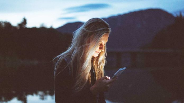 Young woman looks at her phone during the night to depict what to consider before announcing pregnancy or miscarriage online.