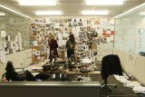 Wide shot office with two cluttered desks, paper files spread over the floor and pictures relating to case on noticeboard.