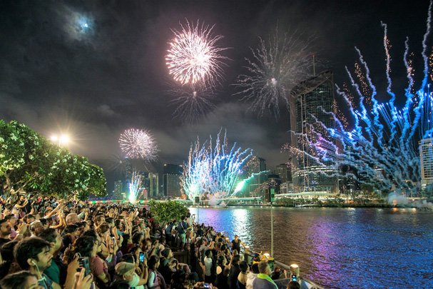 Hundreds of people standing in front of river watching fireworks