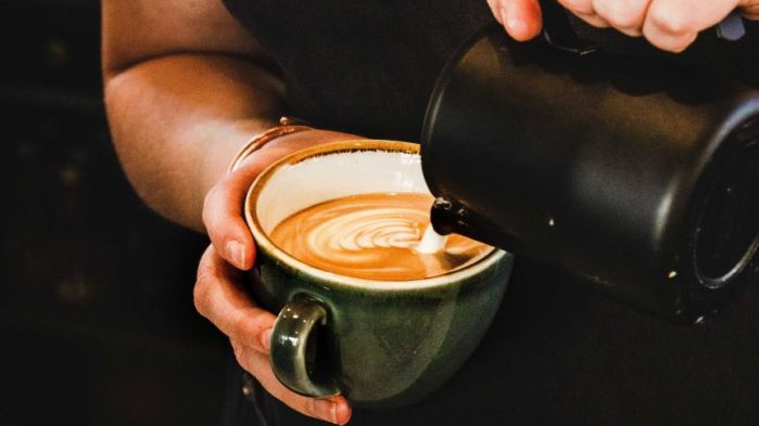 A woman pours milk into a mug of coffee.