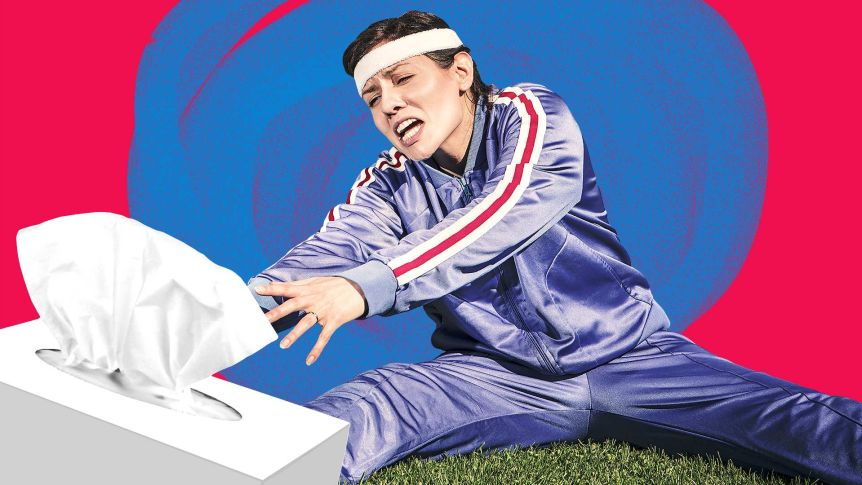 A woman in exercise tracksuit reaches for a box of tissues raising the question whether she should be exercising with a cold?
