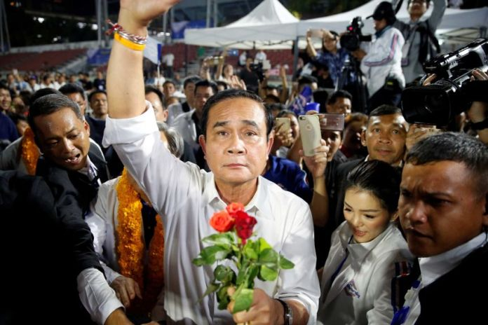 A man standing in a crowd clutching a bouquet of flowers