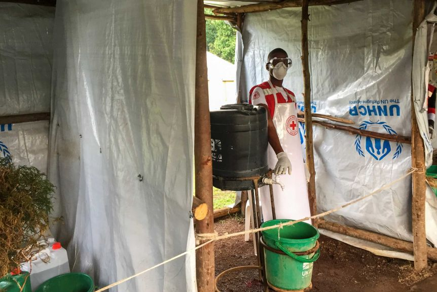 A health worker wears a mask and apron and walks into a makeshift health clinic to pour water