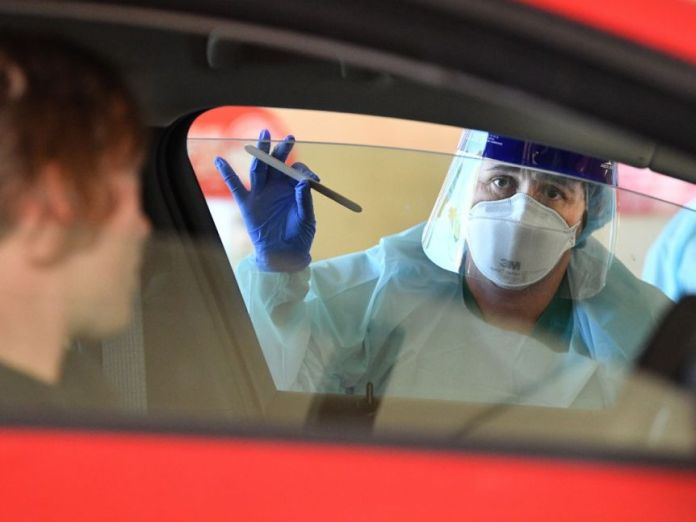 Someone with bioprotective equipment including a mask, standing in the passenger side window holding a swab test.