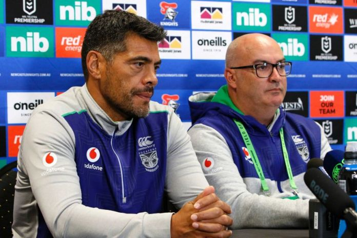 A rugby league coach and the manager of his team sit at a desk during a press conference.