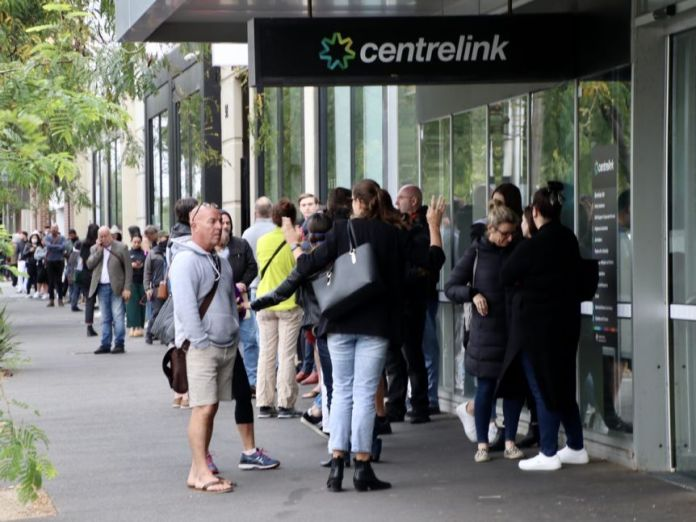 A line of people spans York Street in southern Melbourne, starting with the entrance to a Centrelink building.