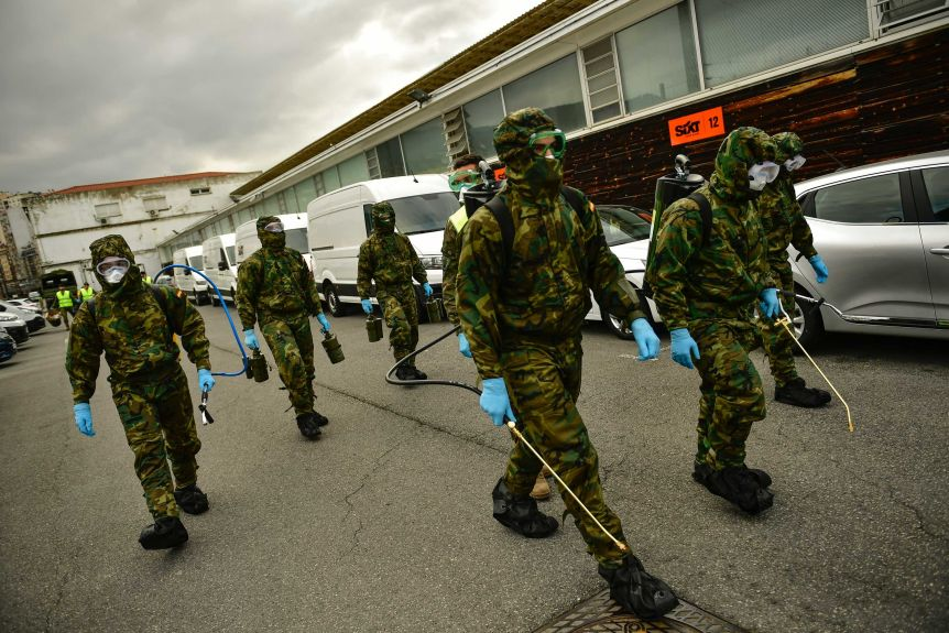 Member of Military Emergency Unit walk with special equipment to disinfect areas
