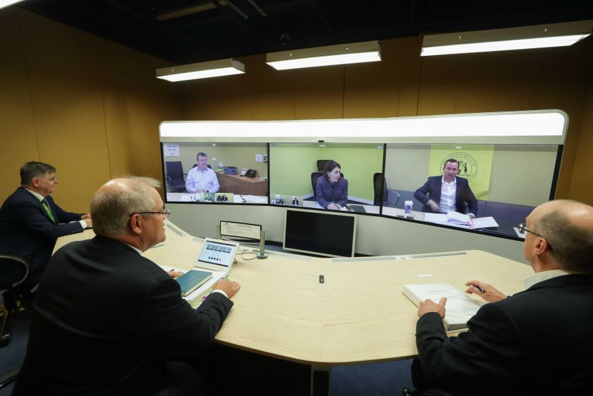 Three men sit at a semi circle table in suits in front of three large screens with one person in each.