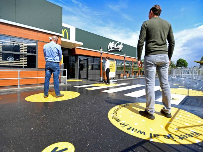 Customers wait outside with social distance signs on McDonald's prototypes in the Netherlands.