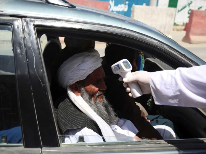 A health worker checks the temperature of an elderly man wearing a turban in a car.