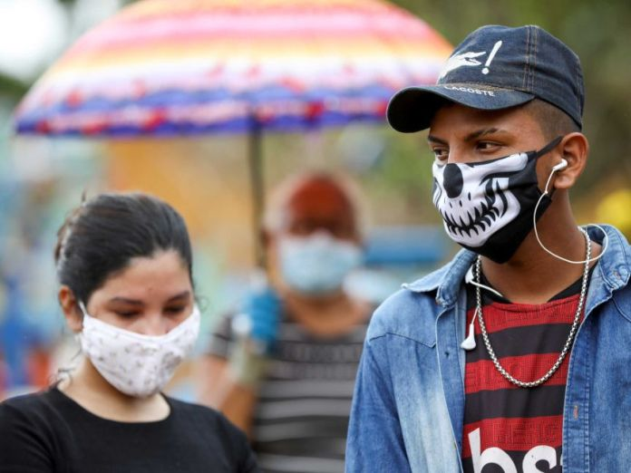 A young man and woman wearing masks at a funeral