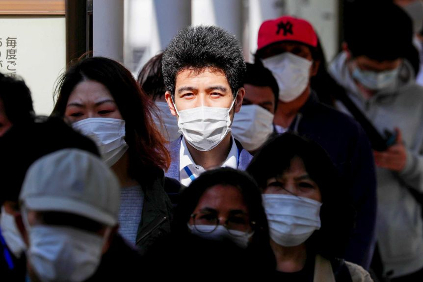 A group of people walking through a Tokyo train station wearing face masks.