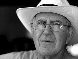 Black and white of older man in white large brimmed hat