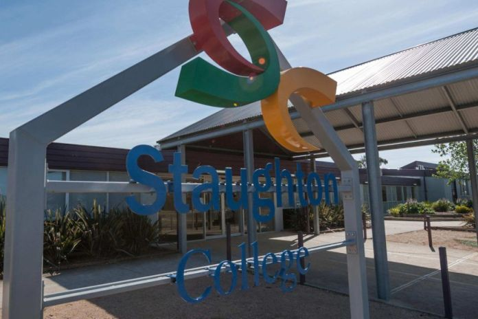 A sign outside a school indicates Staughton College on a sunny blue sky day.