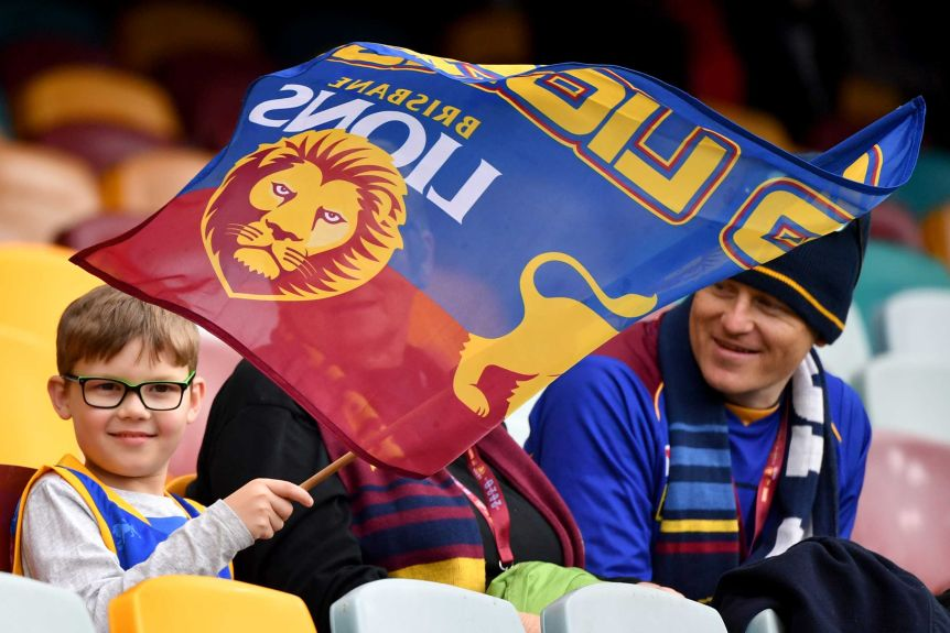 A young Brisbane Lions fan waves a flag as he smiles next to two adults in the stands at the Gabba.