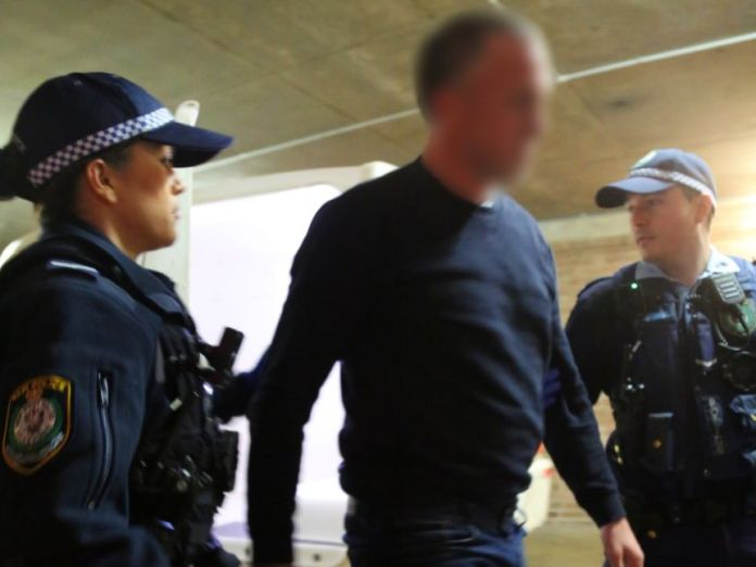 A man is led by two police officers.
