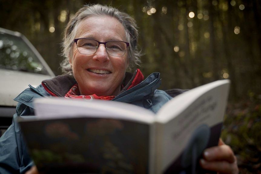 A woman sits outside reading a book.