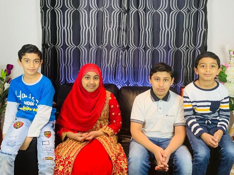 Hasan Razvi, Maryam Razvi, Hamza Razvi and Hussain Razvi sitting on a sofa in the family home.