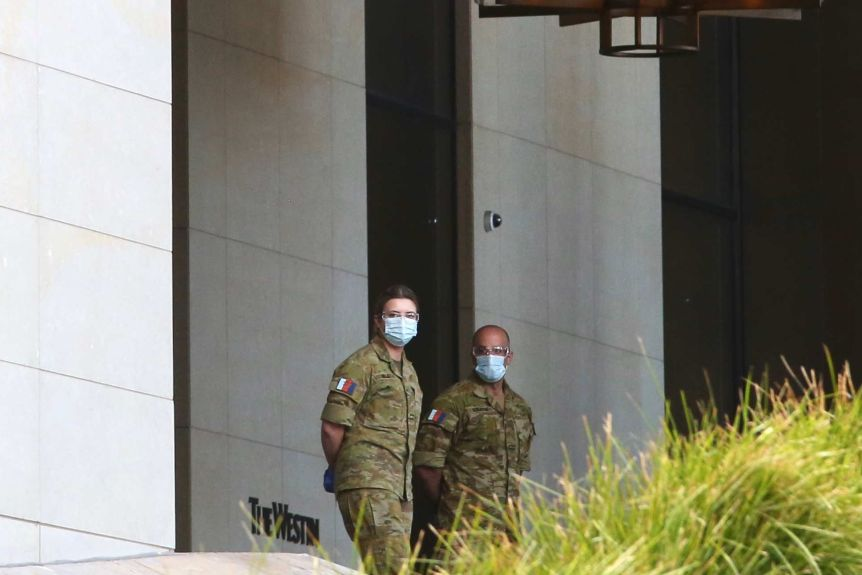 Two ADF personnel wearing face masks stand near the entrance to the Westin Hotel in Perth.
