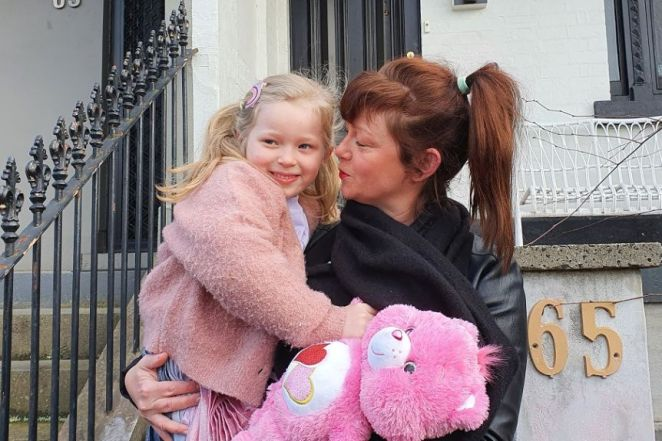 Caitlyn holds her smiling daughter Norah and a pink bear, in a urban residential street in Melbourne.