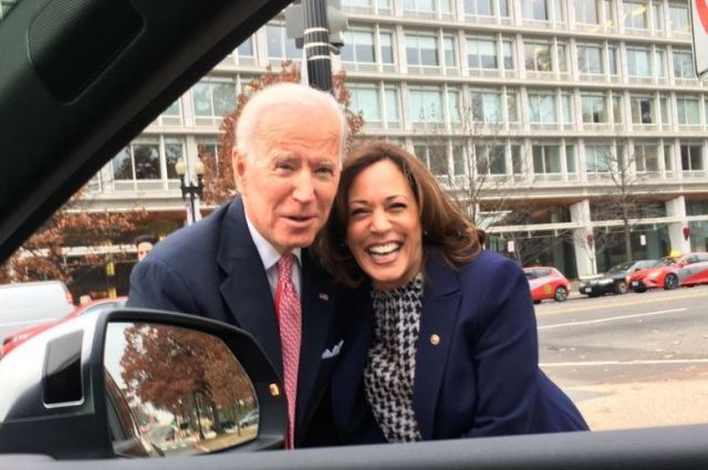 Joe Biden and Kamala Harris posing together and smiling while a photo is taken through a car window