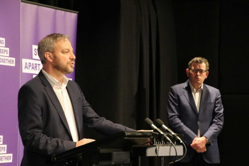 Brett Sutton speaks at a press conference while Premier Daniel Andrews looks on.