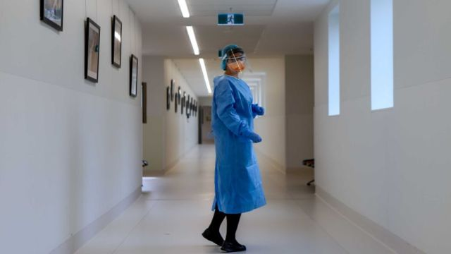 A nurse stands in PPE in a hospital corridor.