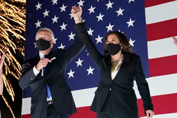 Joe Biden and Kamala Harris raise their hands together in front of a US flag as fireworks explode behind them