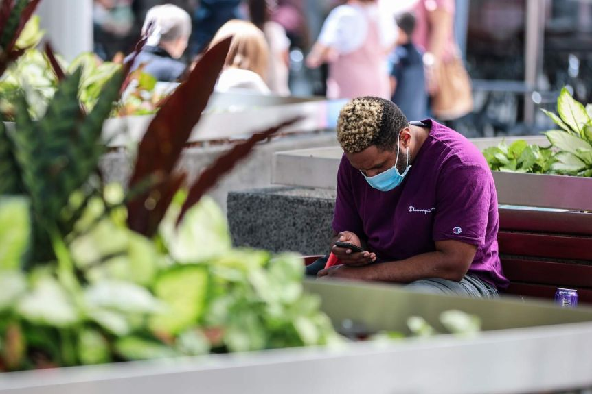 A man wearing a face mask sat down and looking at his phone