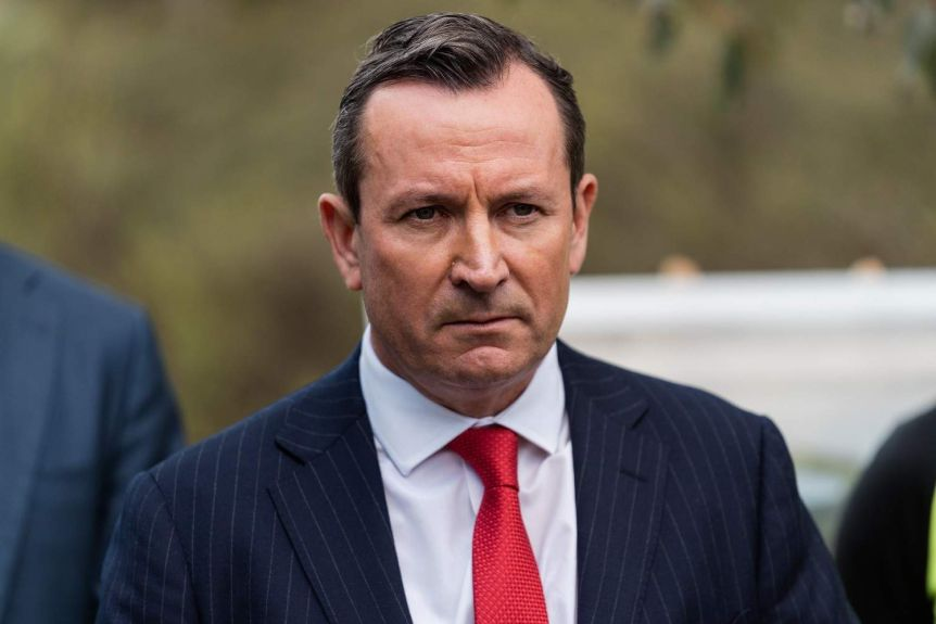 A close up of Mark McGowan wearing a blue suit and red tie, with a stern expression on his face.