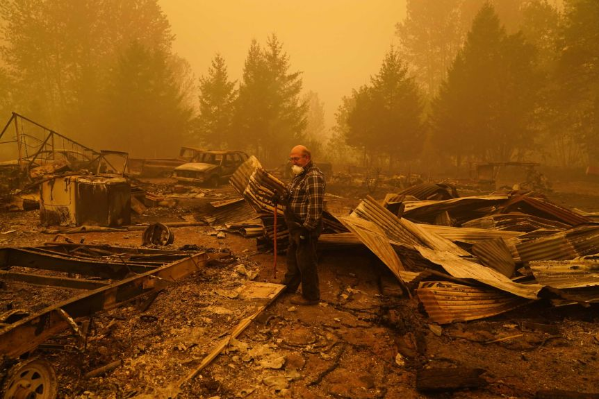 A man stands in the wreckage of his fire destroyed home with an orange sky.
