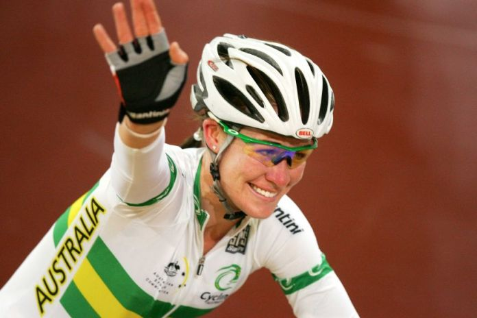 Wearing an Australian jersey, Kate Bates smiles and waves while riding her bike