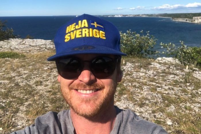 A man taking a selfie at the edge of a cliff wearing a blue and yellow hat with the swedish flag.