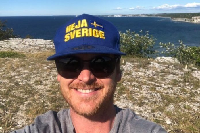 A man taking a selfie on the edge of a cliff wearing a blue and yellow hat with the Swedish flag on it.