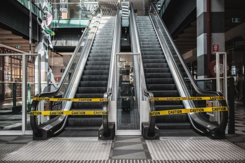 Escalators are closed off with yellow tape reading 'caution'.