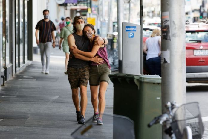 A man and a woman, each wearing a mask, hold each other while walking on a city street.