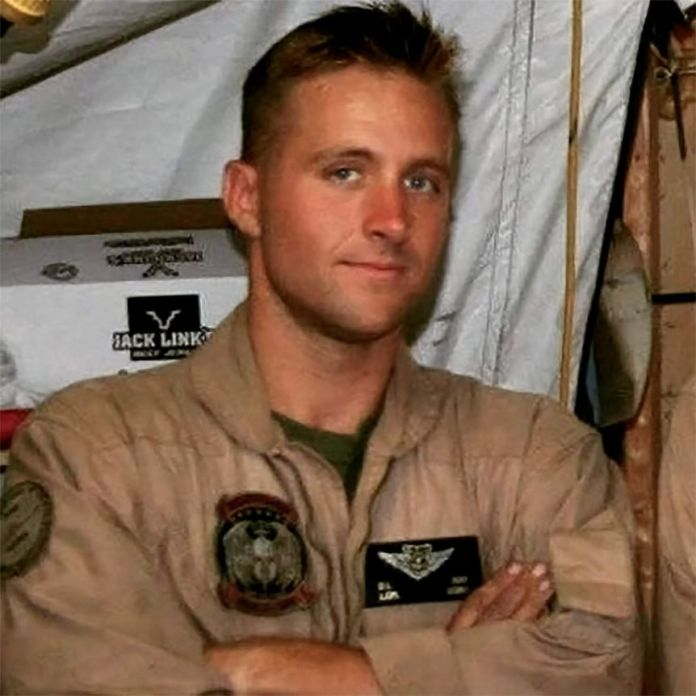 A young man in uniform in a tent.