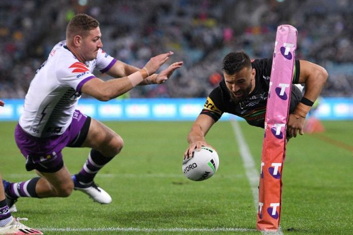 Josh Mansour soars through the air in the corner of the field, rugby ball in hand.