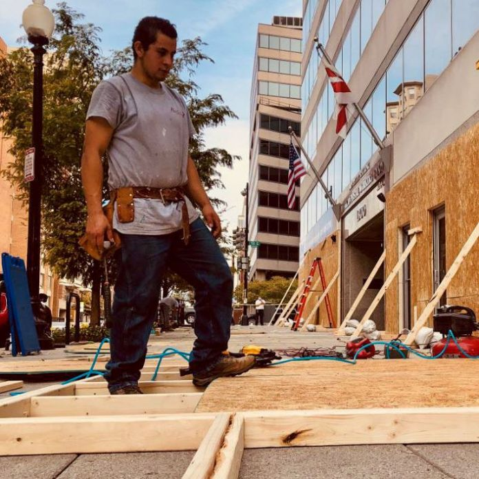 A construction worker looks at wooden planks on a Washington DC street