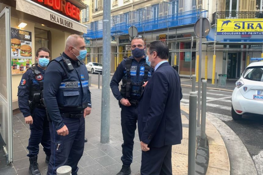 Christian Estrosi stands to the right as he speaks with three police officers in what appears to be the city centre of Nice.
