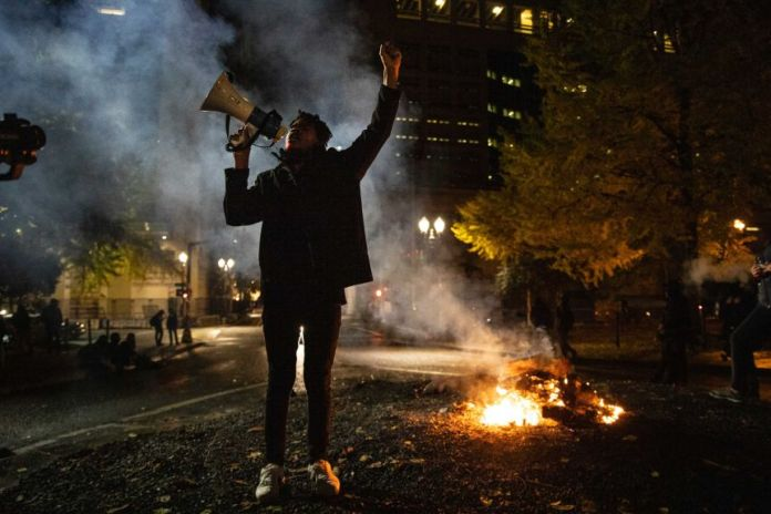 A black woman with a megaphone raises her arm as a fire burns behind her in a smoky city park.