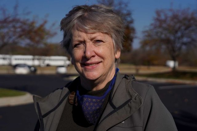 A woman with grey hair and wearing an I voted badge smiles as she stares at the camera.